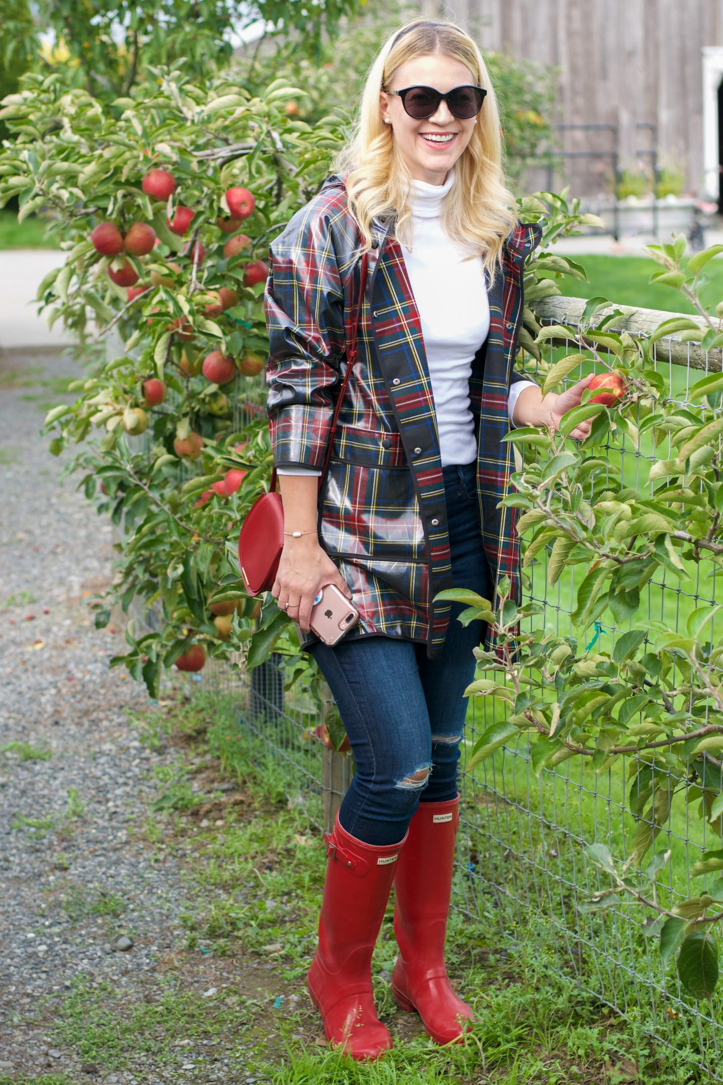 whit wanders fall activities | zara plaid raincoat hunter boots | Fall Activities by popular Seattle lifestyle blog, Whit Wanders: image of a woman in a apple orchard and wearing a Zara plaid rubberized rain coat, white turtle neck, jeans, and red Hunter rain boots.