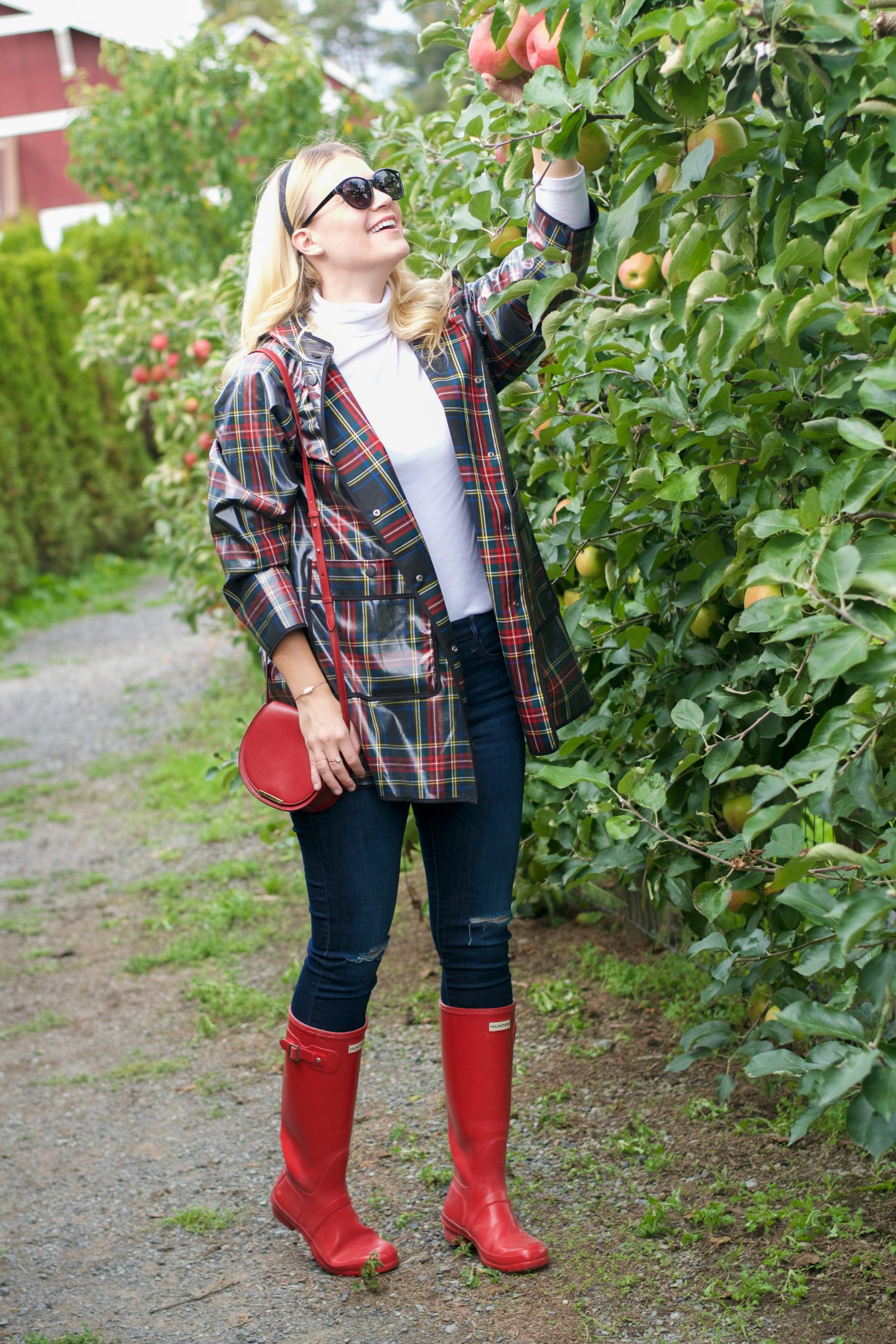 plaid raincoat apple picking hunter boots | zara plaid raincoat hunter boots | Fall Activities by popular Seattle lifestyle blog, Whit Wanders: image of a woman in a apple orchard and wearing a Zara plaid rubberized rain coat, white turtle neck, jeans, and red Hunter rain boots.