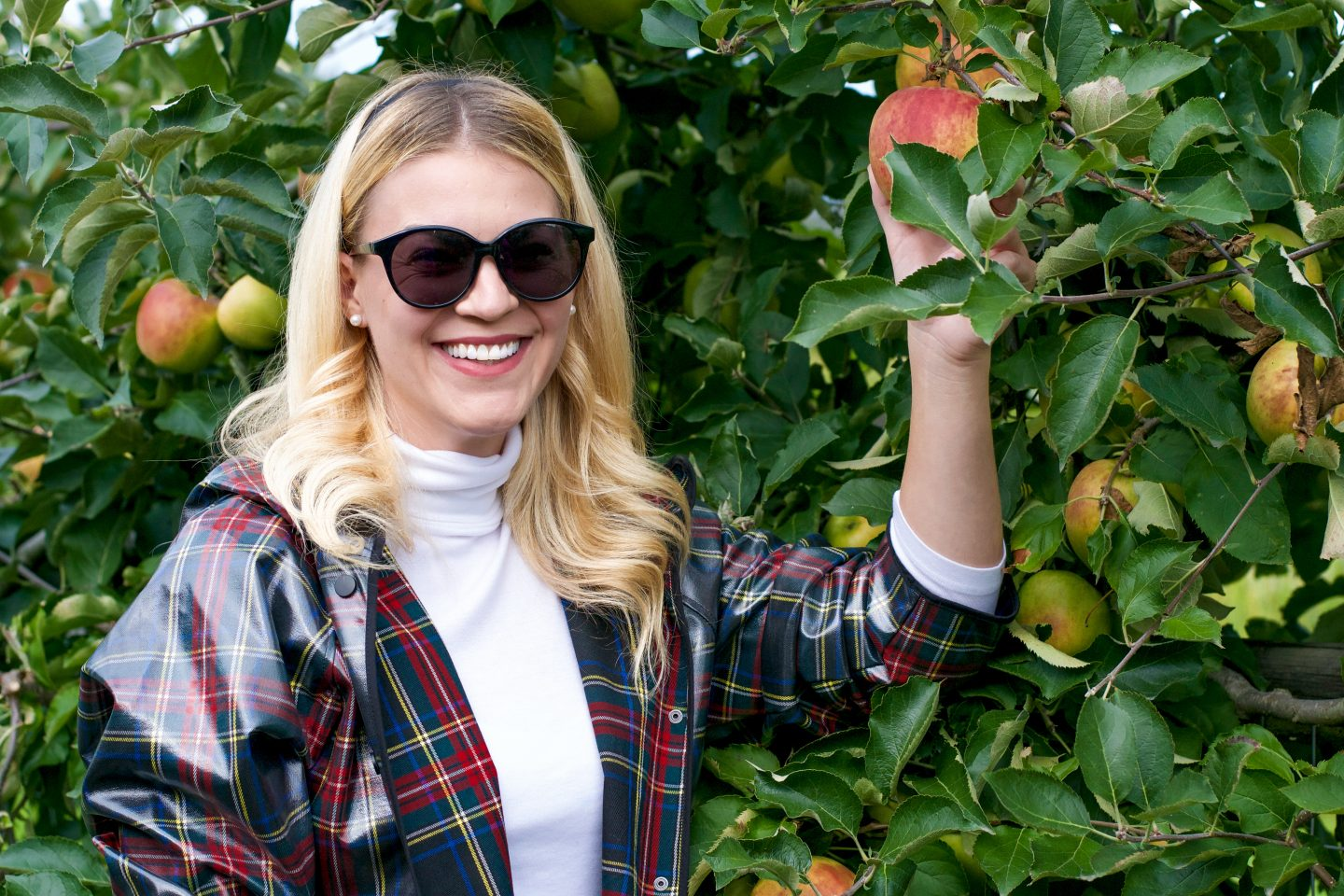 zara plaid raincoat hunter boots   Fall Activities by popular Seattle lifestyle blog, Whit Wanders: image of a woman in a apple orchard and wearing a Zara plaid rubberized rain coat, white turtle neck, jeans, and red Hunter rain boots.
