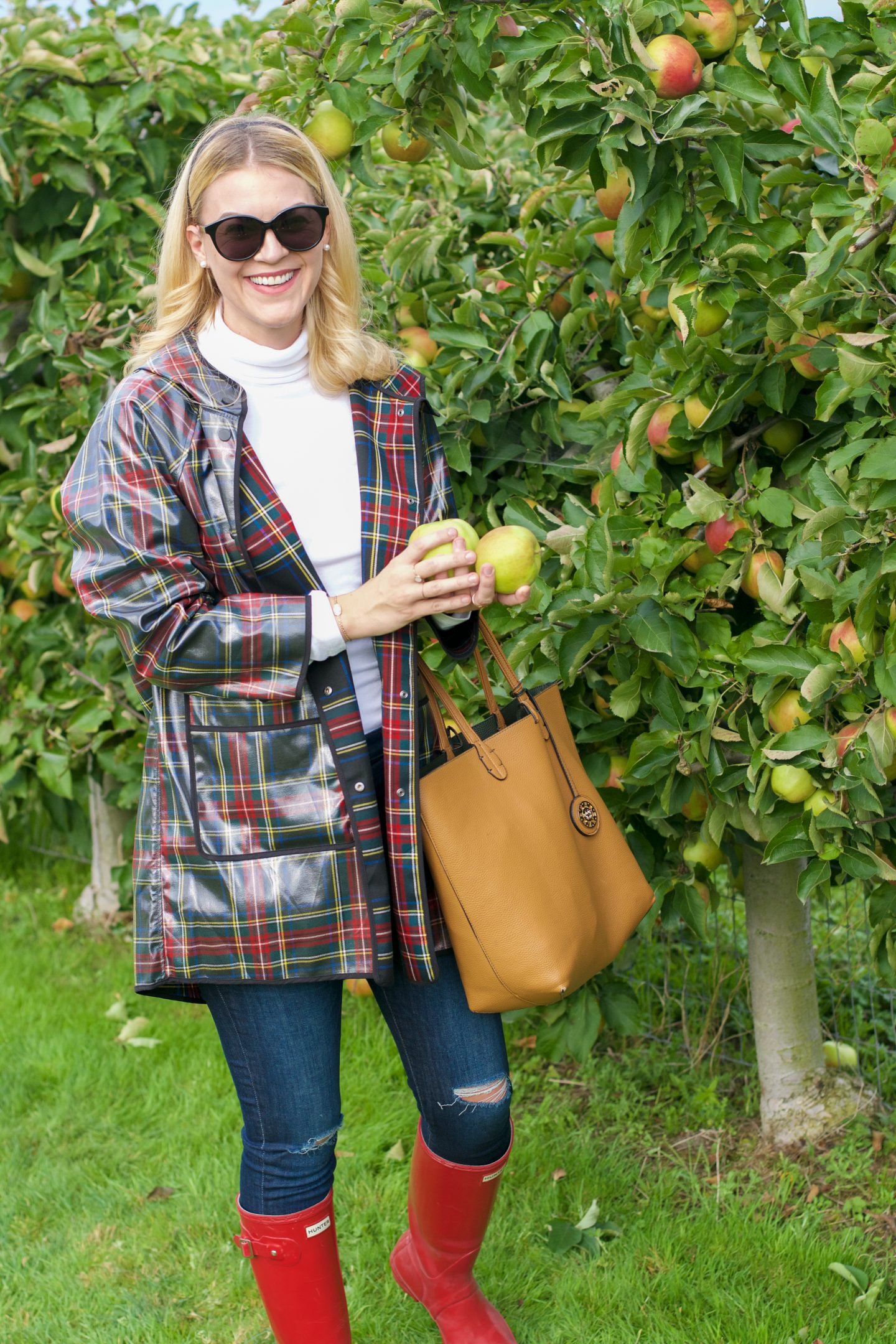 Fall Activities Apple picking | zara plaid raincoat hunter boots | Fall Activities by popular Seattle lifestyle blog, Whit Wanders: image of a woman in a apple orchard and wearing a Zara plaid rubberized rain coat, white turtle neck, jeans, and red Hunter rain boots.