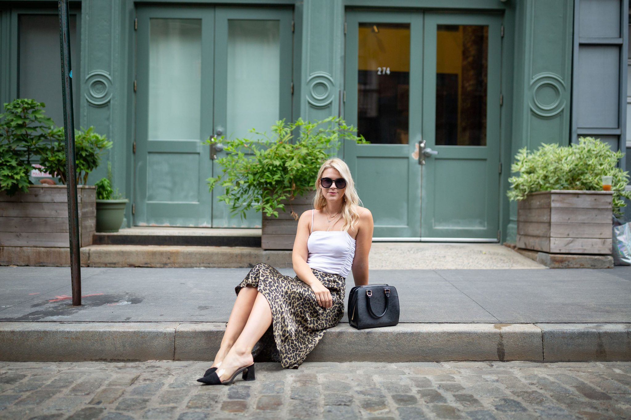 Leopard Skirt by popular Seattle tall fashion blog, Whit Wanders: image of a woman sitting on the curb of a cobble stone street in front of a green building and wearing a Free People Bodysuit, Zara Leopard Skirt, Zara Black Heels, and holding Louis Vuitton Tote.
