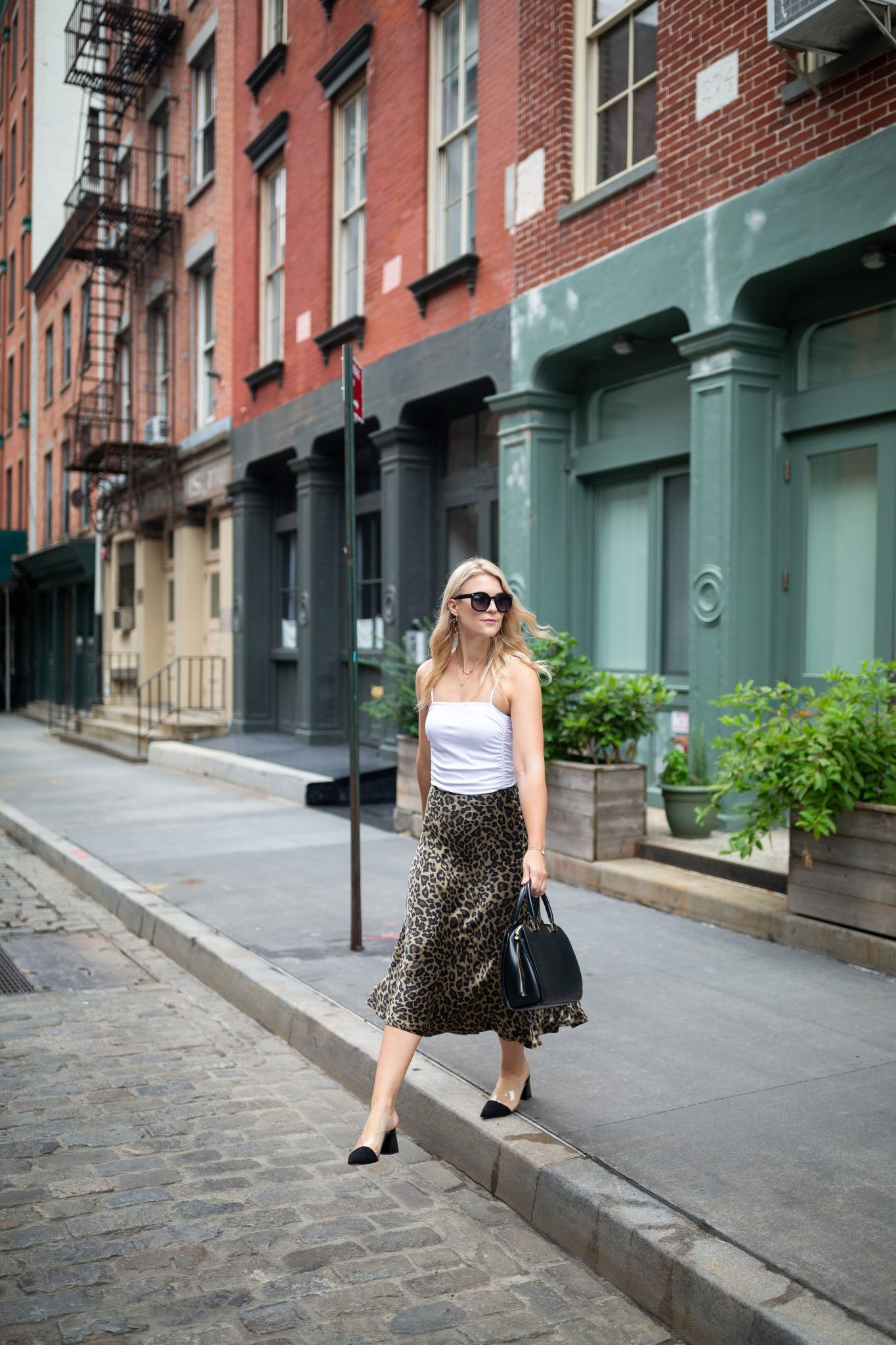 Leopard Skirt by popular Seattle tall fashion blog, Whit Wanders: image of a woman stepping off the curb of a cobble stone street in front of a green building and wearing a Free People Bodysuit, Zara Leopard Skirt, Zara Black Heels, and holding Louis Vuitton Tote.
