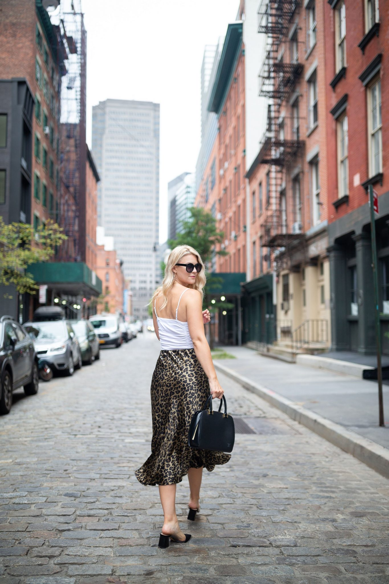 Leopard Skirt by popular Seattle tall fashion blog, Whit Wanders: image of a woman walking down a cobblestone street and wearing a Free People Bodysuit, Zara Leopard Skirt, Zara Black Heels, and holding Louis Vuitton Tote.
