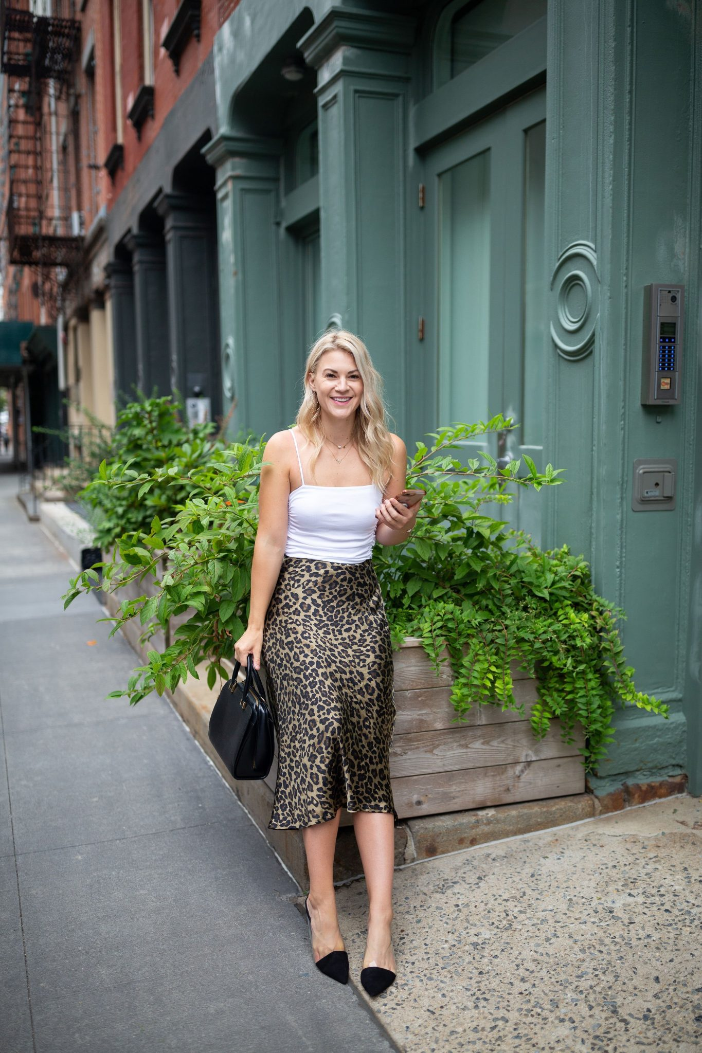 Leopard Skirt by popular Seattle tall fashion blog, Whit Wanders: image of a woman sitting on a garden box in front of a green building and wearing a Free People Bodysuit, Zara Leopard Skirt, Zara Black Heels, and holding Louis Vuitton Tote.