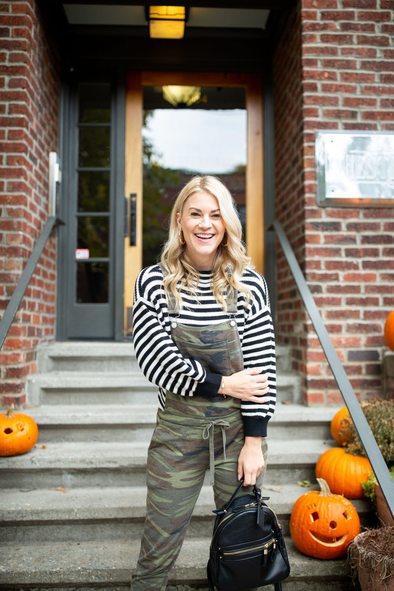 Camo Overalls by popular Seattle tall fashion blog, Whit Wanders: image of a woman sitting on some stairs while holding a pumpkin and wearing a black and white sweater with a pair of camo overalls.
