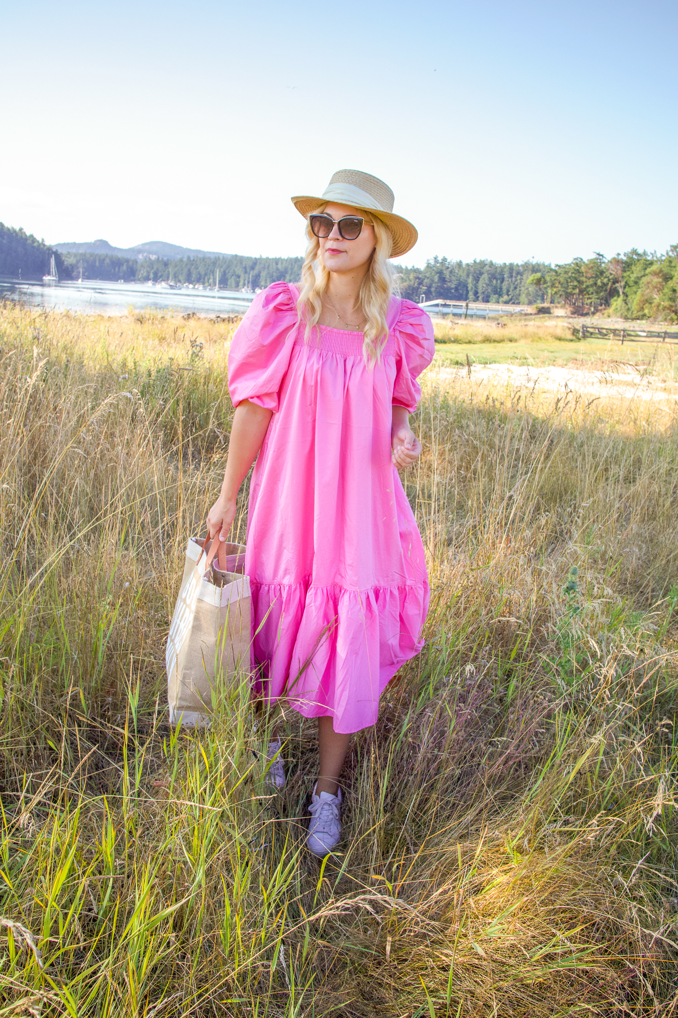 H&M Dress by popular Seattle fashion blog, Whit Wanders: image of a woman walking outside on San Juan island and wearing a H&M pink puff-sleeved dress, straw boater hat, and cat eye sunglasses.