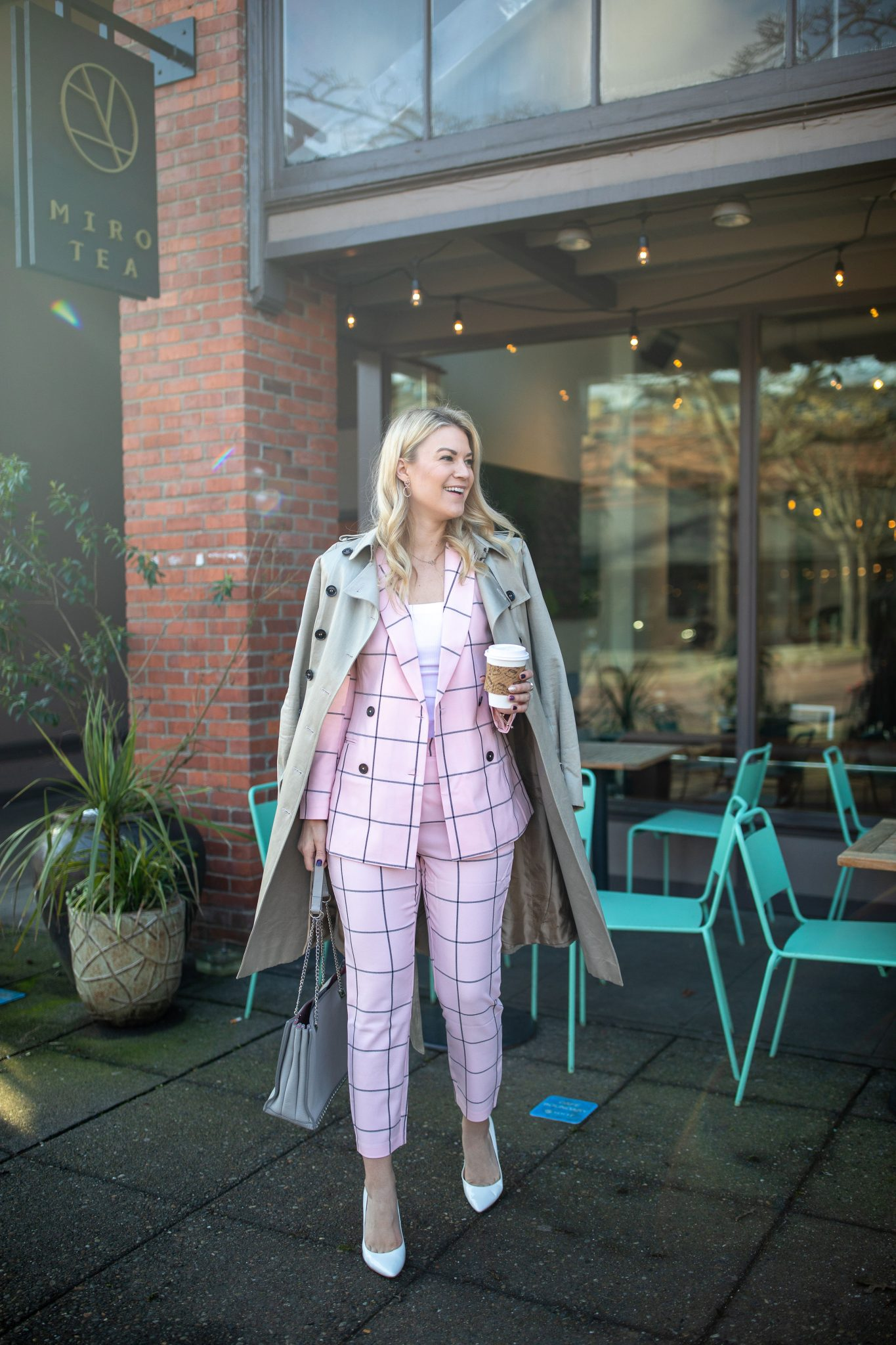ASOS Pink Suit styled for work by top Seattle tall fashion blogger, Whit Wanders: image of a woman standing in front of a coffee shop and wearing a Burberry Trench Coat, ASOS Grid Suit, Sam Edelman Heels, and holding a Zara Purse.