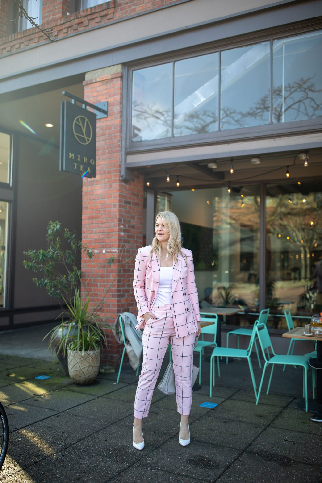 ASOS Pink Suit styled for work by top Seattle tall fashion blogger, Whit Wanders: image of a woman standing in front of a coffee shop and wearing a ASOS Grid Suit, Sam Edelman Heels, and holding a Zara Purse.