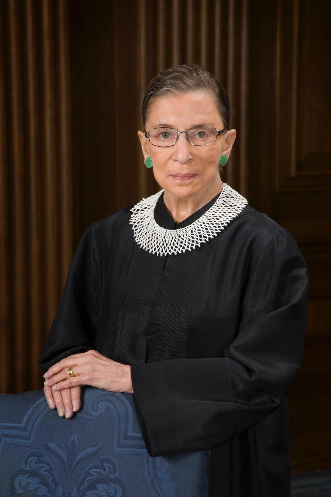 Ruth Bader Ginsburg Quotes by popular Seattle lifestyle blog, Whit Wanders: image of Ruth Bader Ginsburg wearing a black Supreme Court Justice robe, white lace collar necklace, and jade earrings.