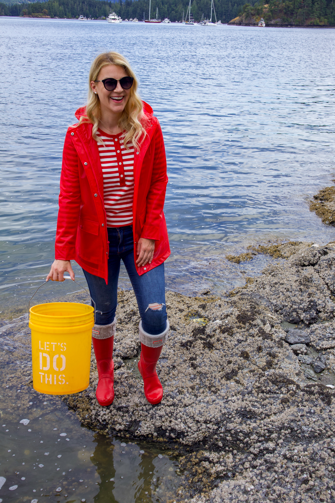Seattle Style by popular Seattle tall fashion blog, Whit Wanders: image of a woman standing by the ocean and wearing a pair of red Hunter rain boots and a Levi's Translucent Rain Jacket.