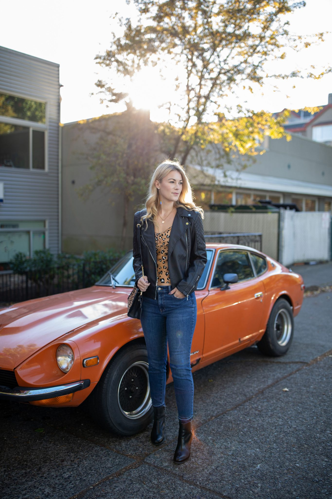 Leather Jacket by popular Seattle tall fashion blog, Whit Wanders: image of a woman standing in front of a orange sports car and wearing a Express Leather Jacket, Nastygal cami, Madewell jeans, Ralph Lauren Black Booties, and holding a Sole Society Purse.