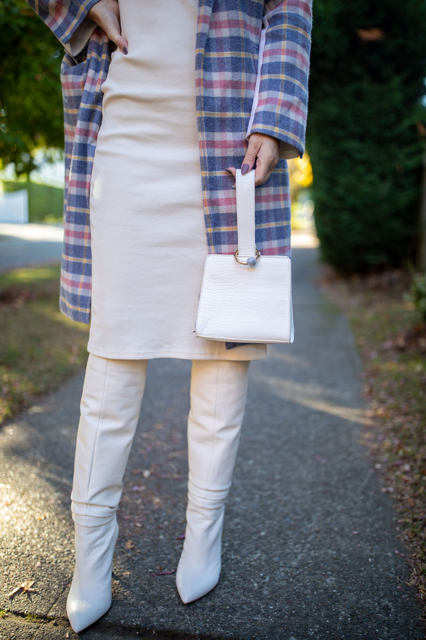 White Dress by popular Seattle tall fashion blog, Whit Wanders: image of a woman standing outside on a sidewalk and wearing a white dress, white otk boots, and a pink, blue, yellow, and white plaid wool jacket.