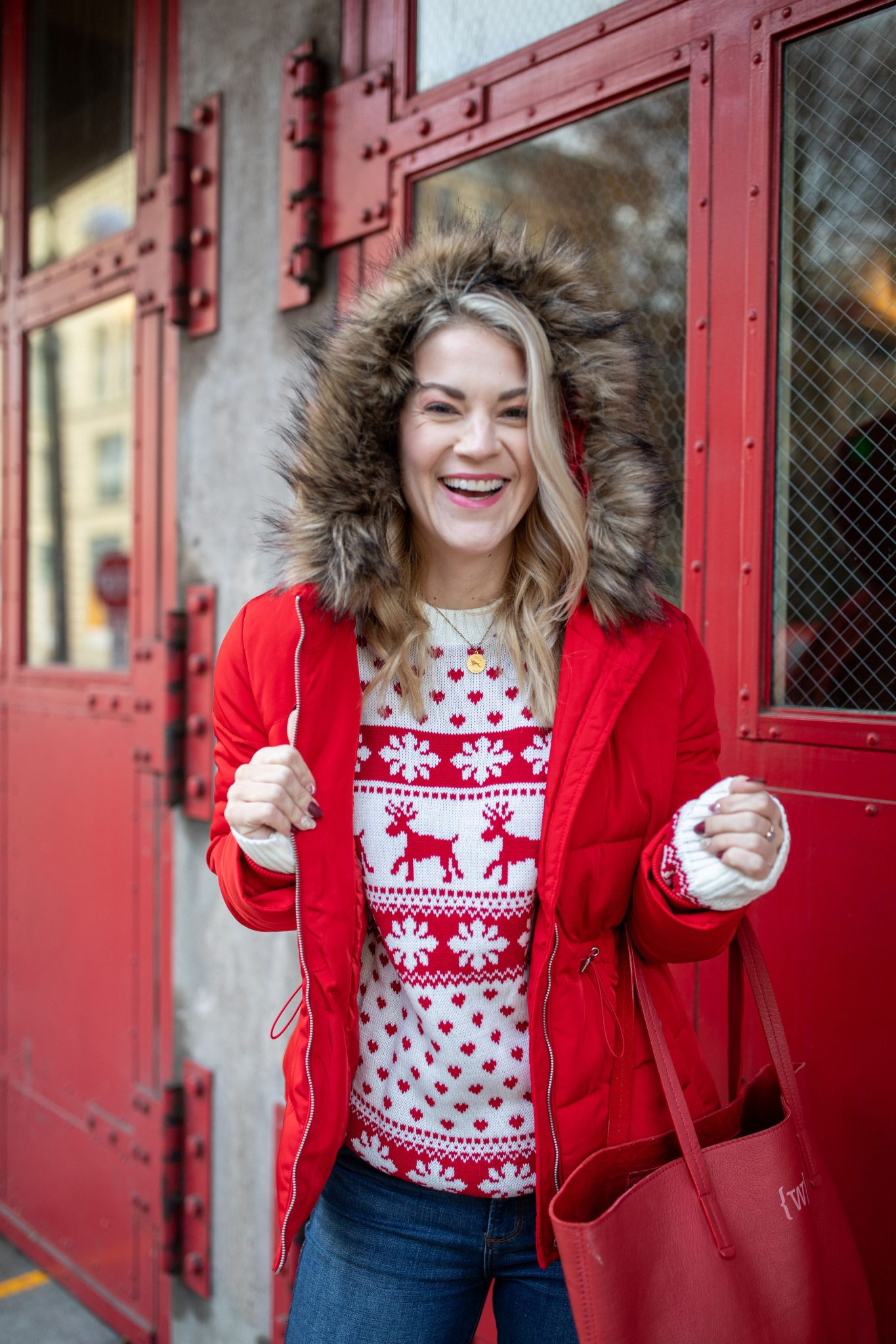 Red Puffer Jacket by popular Seattle tall fashion blog, Whit Wanders: image of a woman standing in front of a red metal door and wearing a red puffer jacket, red and white holiday sweater, and jeans.