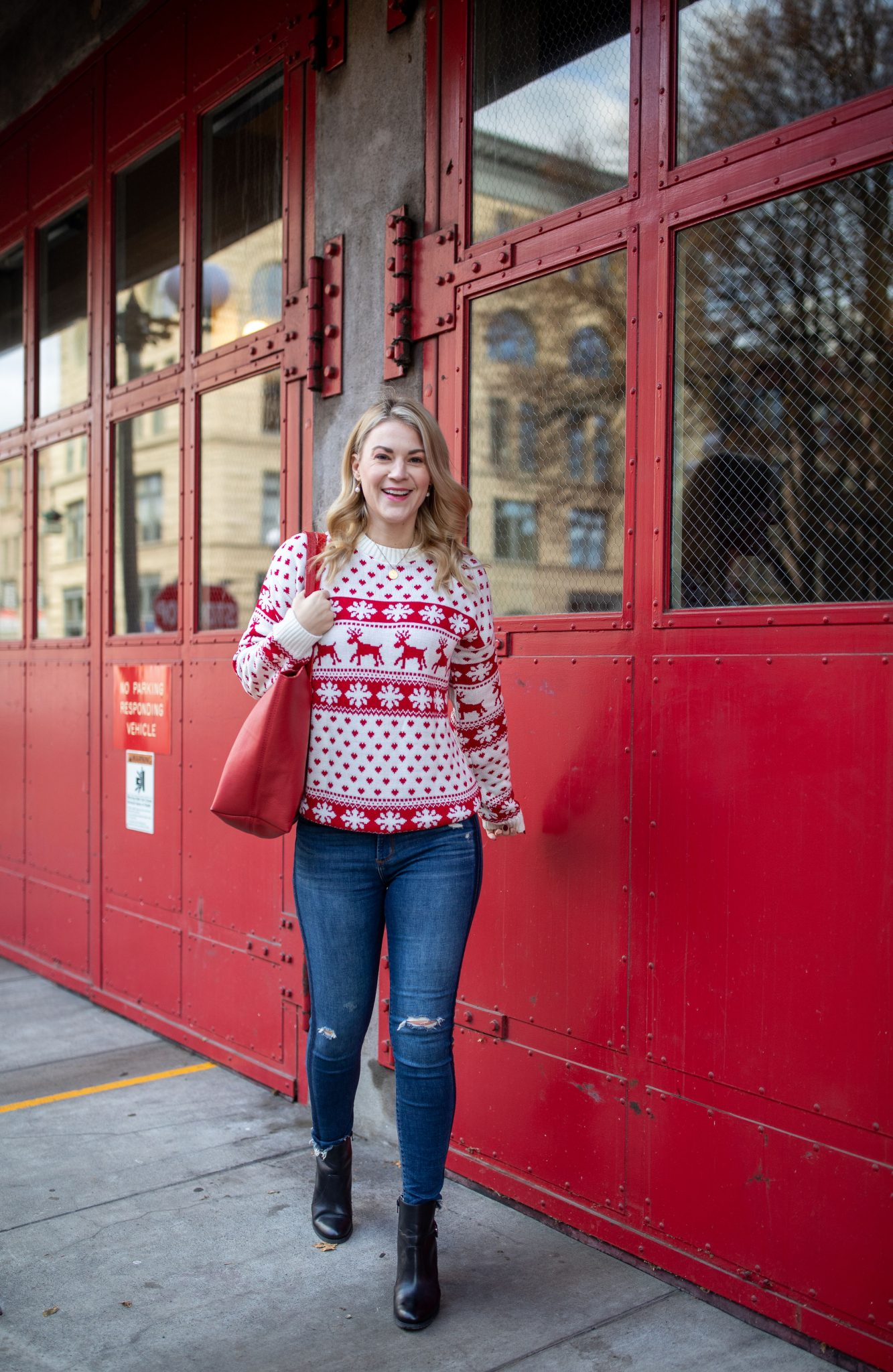 Red Puffer Jacket by popular Seattle tall fashion blog, Whit Wanders: image of a woman standing in front of a red metal door and wearing a red and white holiday sweater, jeans and black ankle boots.