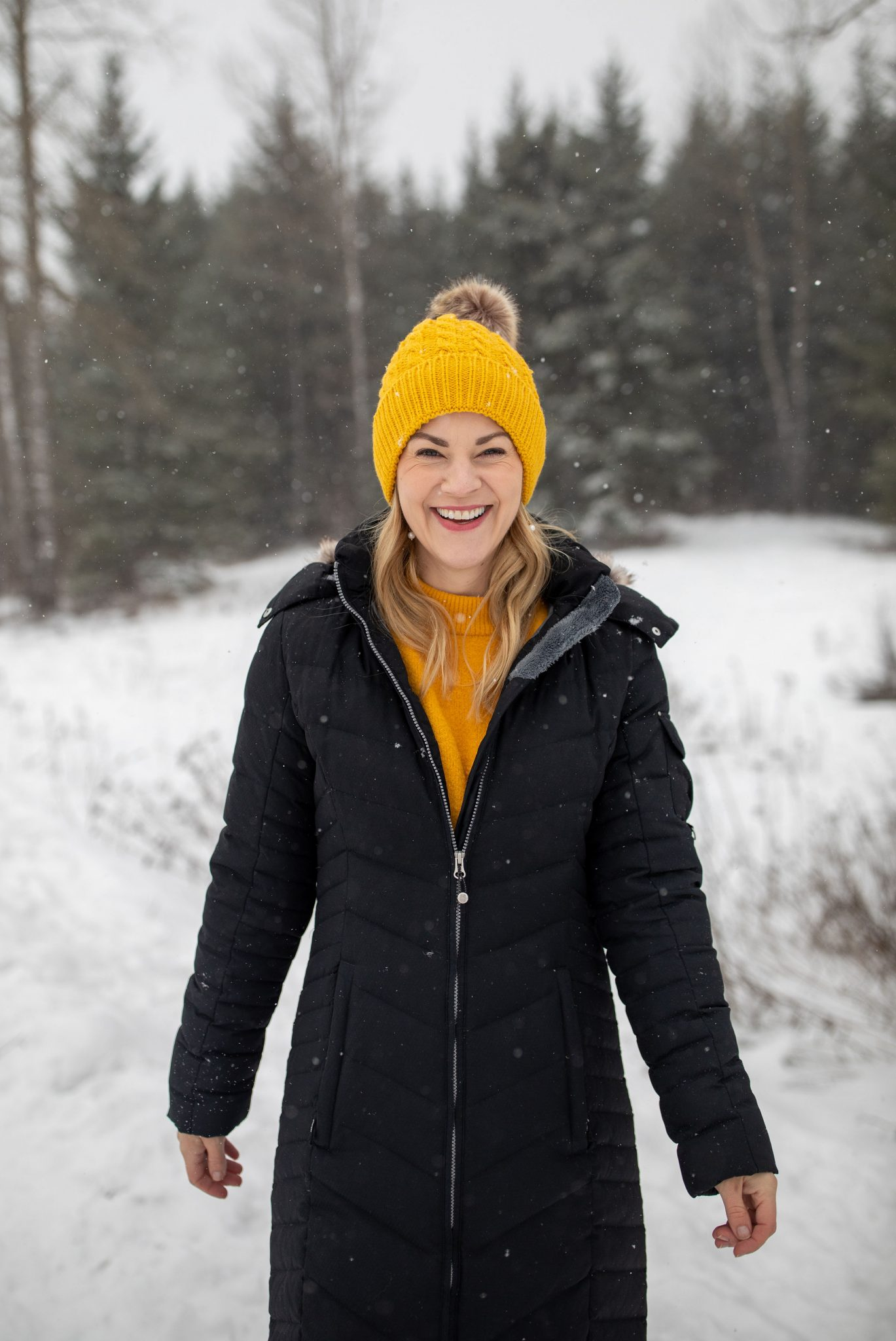 Down Jacket by popular Seattle tall fashion blog, Whit Wanders: image of a woman walking outside in the snow and wearing a yellow beanie, yellow sweater, and black down jacket.