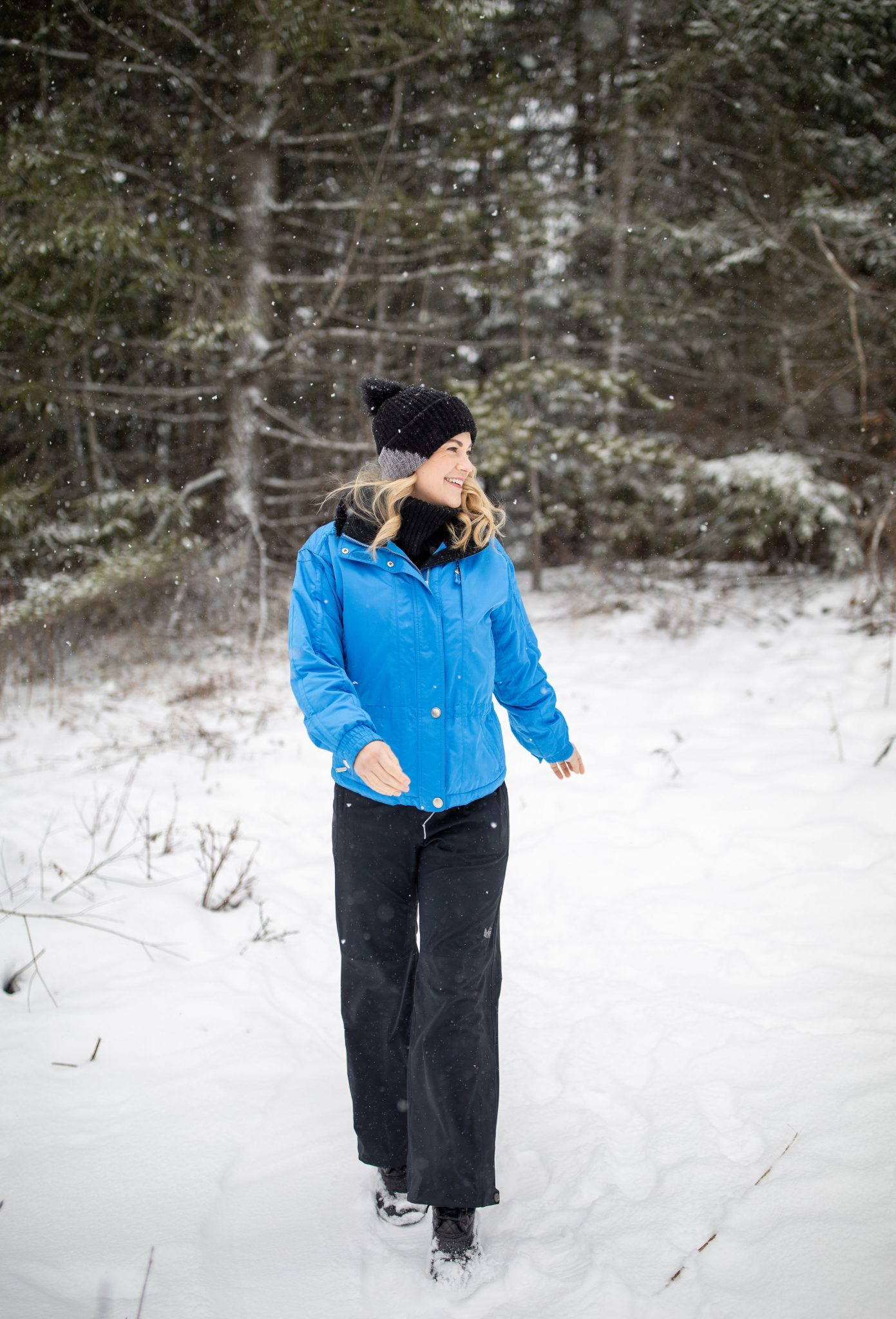 Ski Style by popular Seattle tall fashion blog, Whit Wanders: image of a woman standing outside in the snow and wearing a blue coat, black knit beanie, black rib knit turtleneck sweater, and black snow pants.