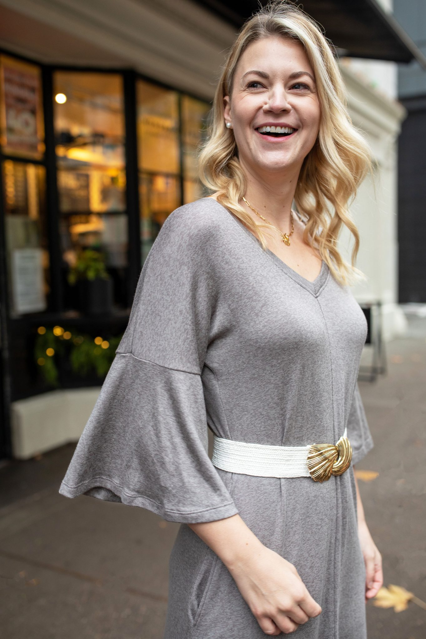 Sweater Dress by popular Seattle tall fashion blog, Whit Wanders: image of a woman standing outside and wearing a Akala sweater dress with a white waist belt and white sneakers.