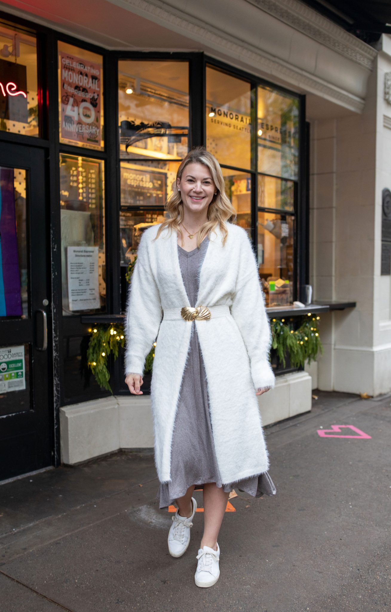 Sweater Dress by popular Seattle tall fashion blog, Whit Wanders: image of a woman standing outside and wearing a Akala sweater dress with a white fuzzy longline sweater, white waist belt and white sneakers.