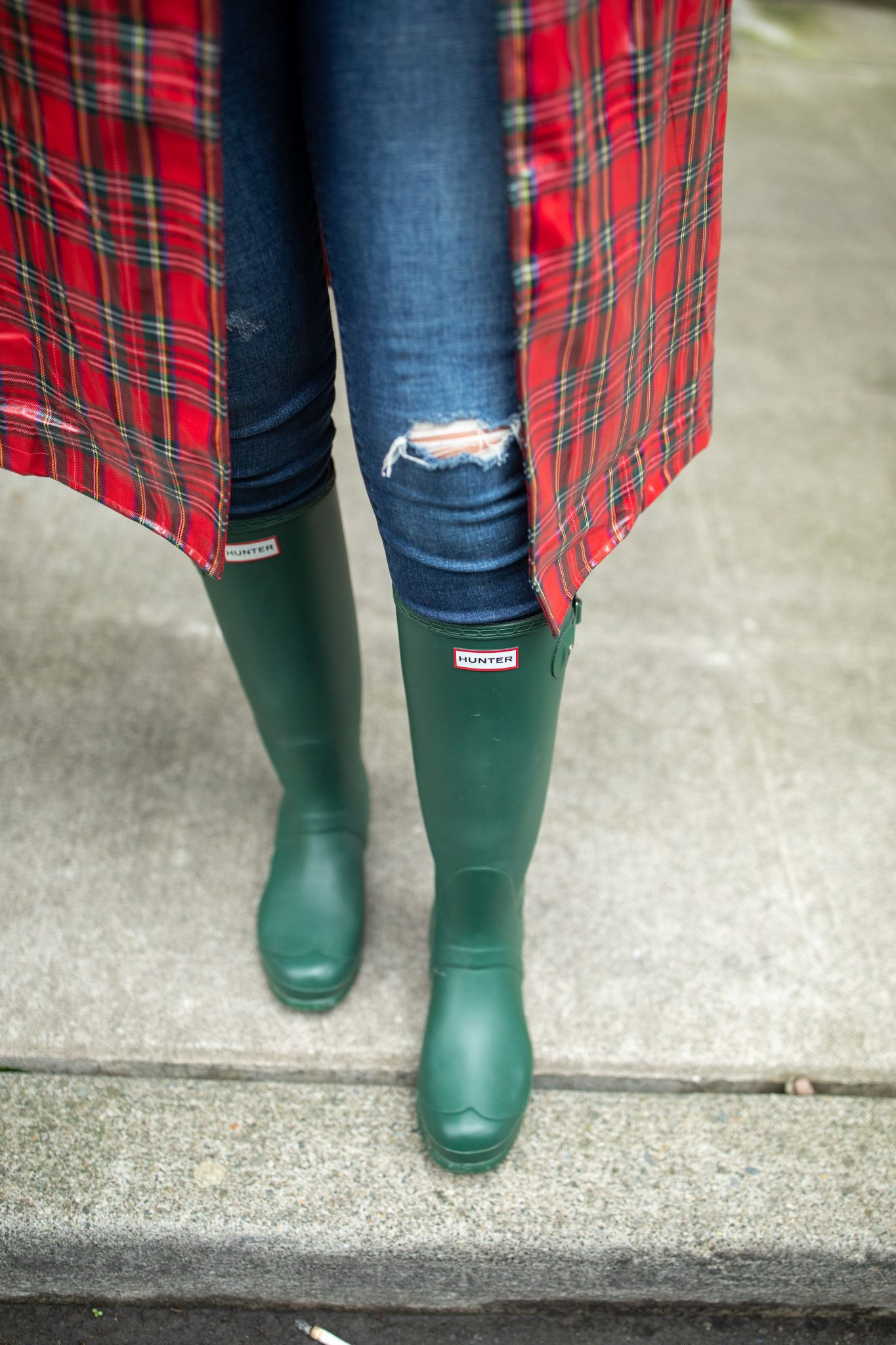 Hunter Boots by popular Seattle tall fashion blog, Whit Wanders: image of a woman walking outside and wearing a red plaid vinyl jacket, black face mask, black hoodie, jeans, and green Hunter boots.