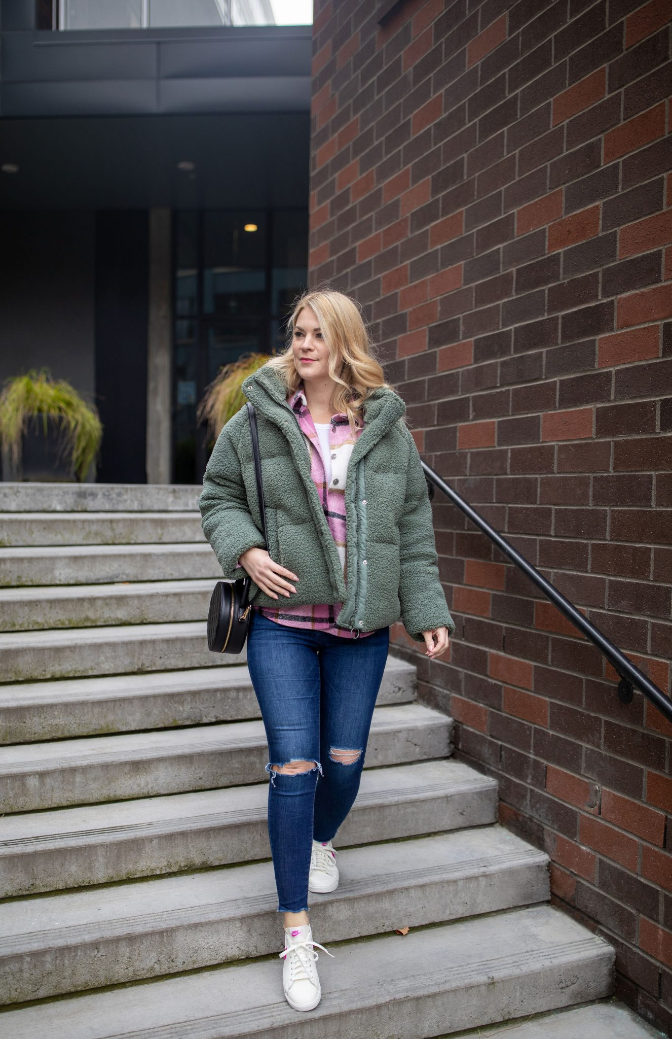 Puffer Jacket by popular Seattle tall fashion blog, Whit Wanders: image of a woman walking down some cement stairs and wearing a green fleece puffer jacket, oversized plaid button down, distressed denim, and white sneakers.