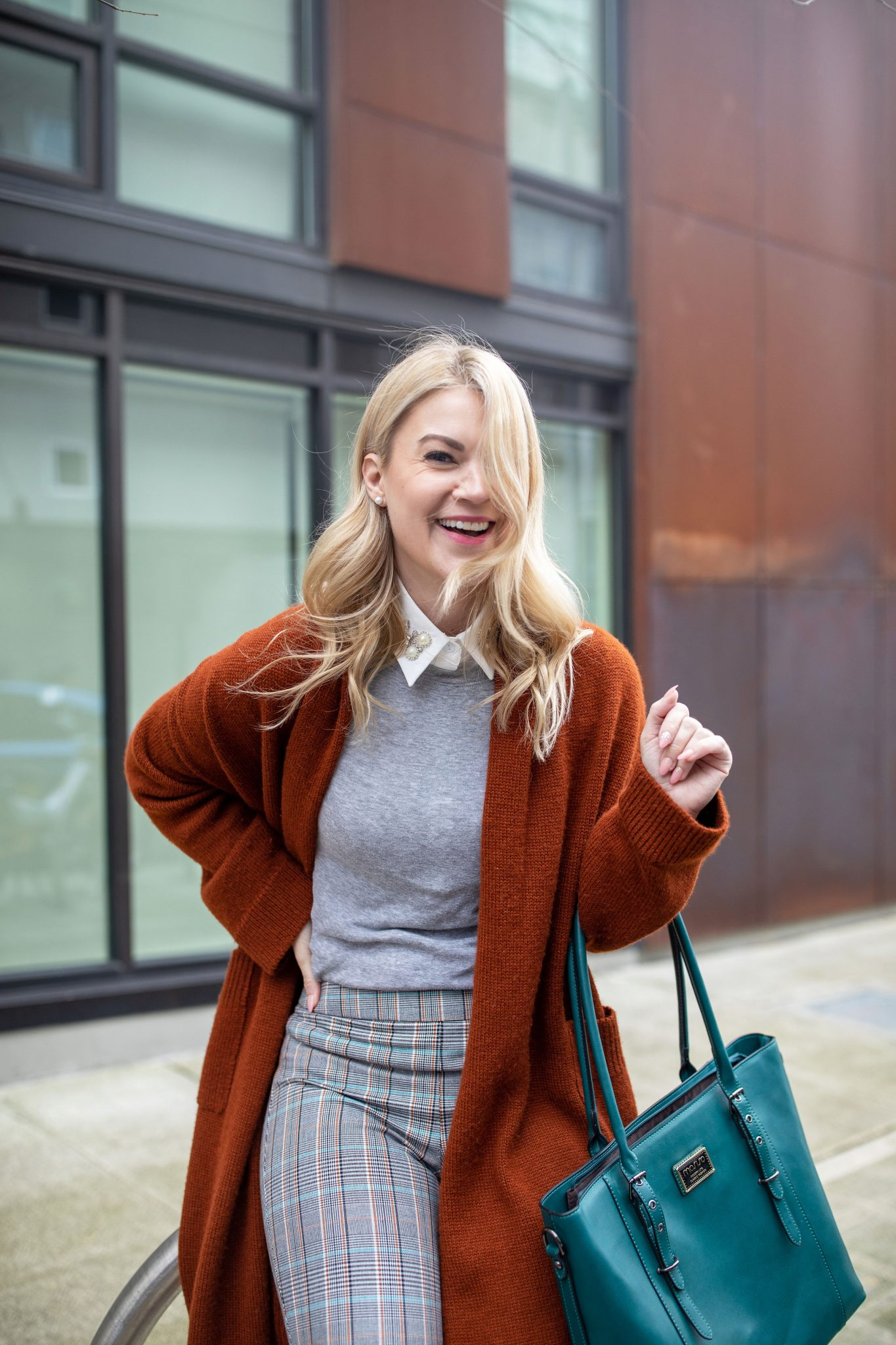 Workwear Style by popular Seattle tall fashion blog, Whit Wanders: image of a woman wearing a rust color duster cardigan, grey sweater, white blouse with bejeweled collar, plaid pants, black heels, and carrying a blue purse.