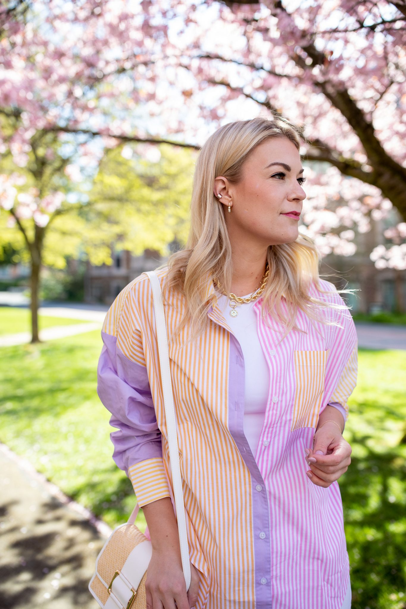 Purple Coat by popular Seattle tall fashion blog, Whit Wanders: image of a woman standing by a tree with pink cherry blossoms and wearing an oversized stripe shirt.